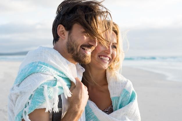 Casal feliz enrolado em cobertor na praia