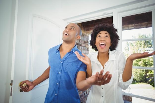 Casal feliz entrando em sua casa e torcendo