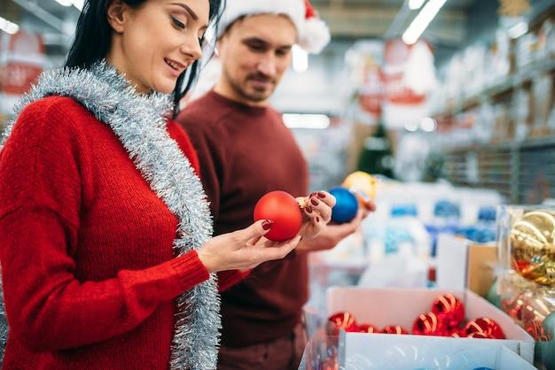 Casal feliz escolhe bolas de árvore de natal no supermercado, tradição familiar. compra de artigos de férias em dezembro