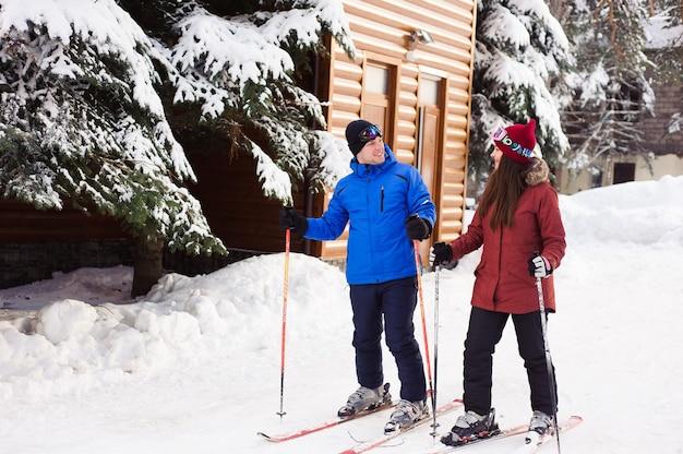 Casal feliz esquiando em uma estação de esqui na floresta