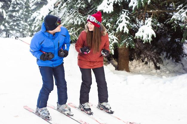 Casal feliz, esquiar em uma estação de esqui na floresta