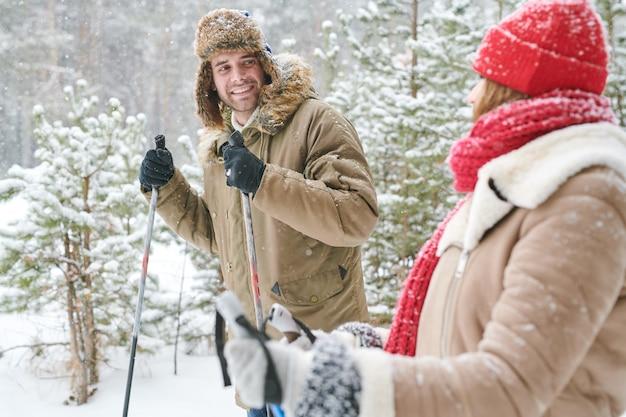 Casal feliz, esquiar na floresta