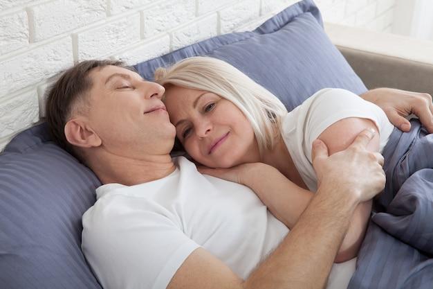 Casal feliz está deitado na cama juntos. apreciando a companhia um do outro.