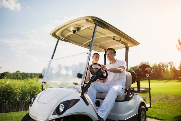 Casal feliz está dirigindo carrinho de golfe pelo campo de golfe.