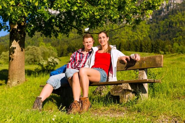 Casal feliz está sentado em um banco com panorama da montanha