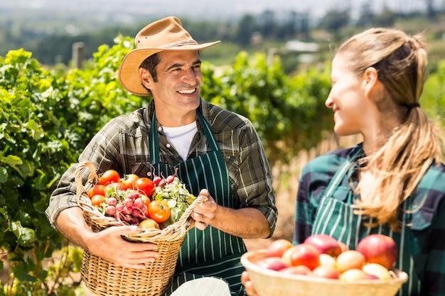 Casal feliz fazendeiro segurando cestas de legumes e frutas