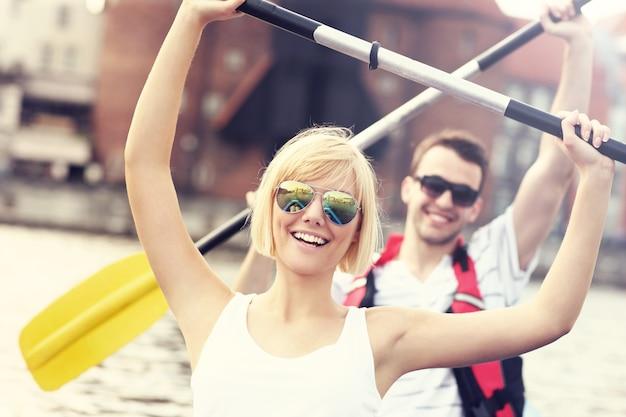 Casal feliz fazendo canoagem no rio motlawa em gdansk, na polônia