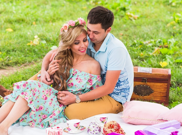 Casal feliz fazendo piquenique romântico no campo.