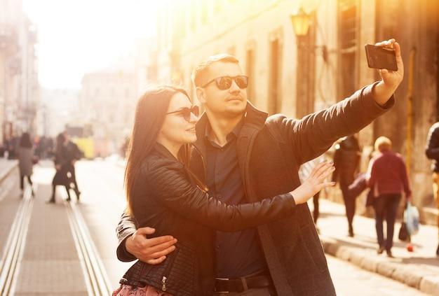 Casal feliz fazendo selfie na rua.