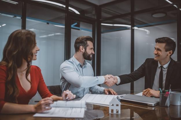 Casal feliz fazendo um acordo com um agente de vendas