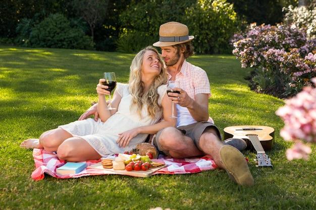 Casal feliz fazendo um piquenique e abraçando no jardim