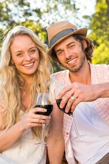 Casal feliz fazendo um piquenique e beber vinho tinto no jardim