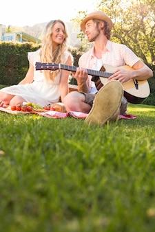 Casal feliz fazendo um piquenique e tocando violão no jardim