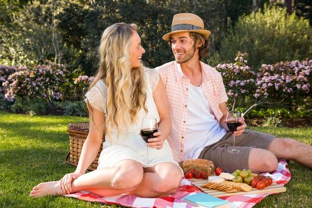 Casal feliz fazendo um piquenique no jardim