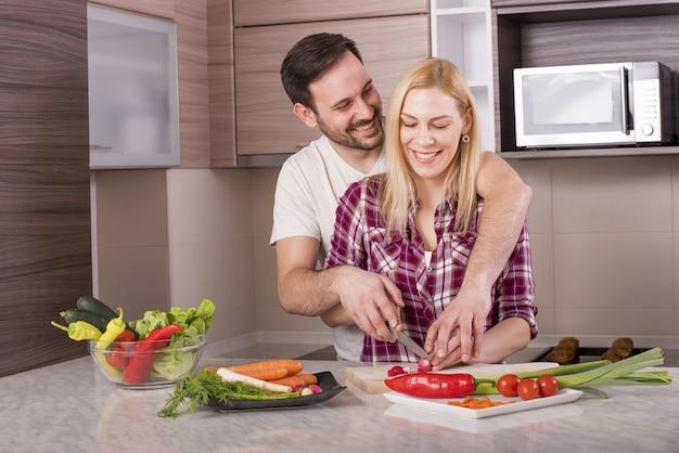 Casal feliz fazendo uma salada fresca com legumes na bancada da cozinha