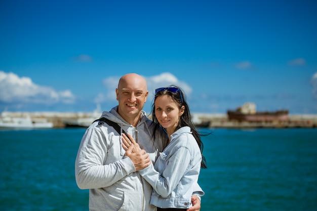 Casal feliz fica no aterro com os braços em volta um do outro no contexto do mar e do céu em um dia ensolarado