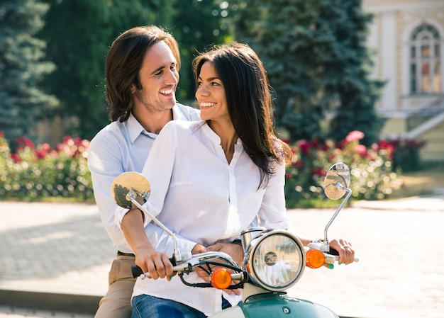 Casal feliz flertando em scooter