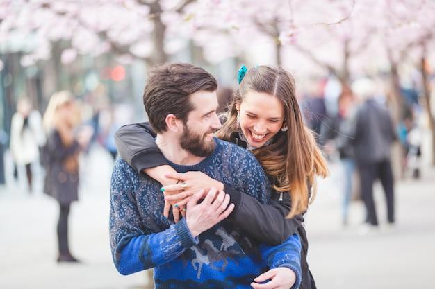 Casal feliz hipster em estocolmo com flores de cerejeira