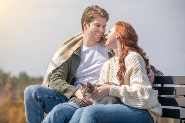 Casal feliz. homem amoroso e atencioso abraçando uma mulher alegre com um gato sentado no banco ao ar livre em um dia ensolarado