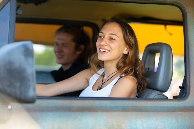 Casal feliz homem e mulher caucasiano dirige uma velha van vintage campista na estrada. viagem de férias em família e viagem de férias.