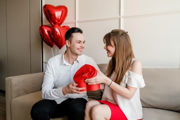 Casal feliz homem e mulher com coração em forma de caixa de presente vermelha e balões no sofá em casa