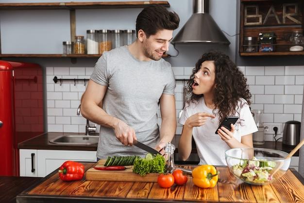 Casal feliz homem e mulher cozinhando salat com legumes juntos na cozinha moderna em casa