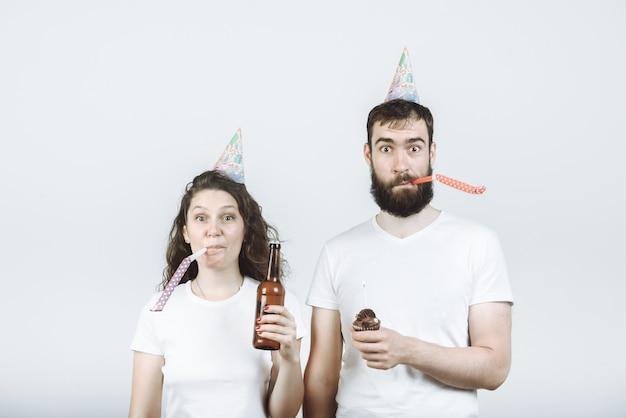Casal feliz, homem e mulher em bonés de festa, soprando na buzina com cerveja e bolo na parede cinza