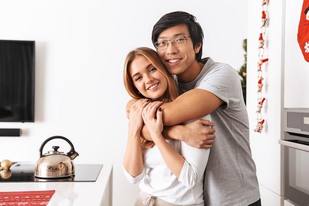 Casal feliz, homem e mulher, em pé na cozinha bem iluminada e se abraçando