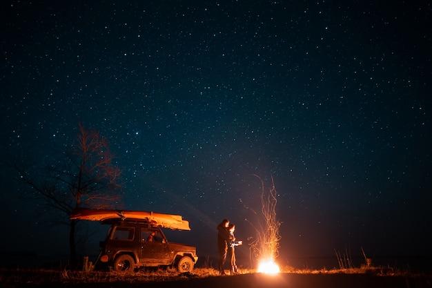 Casal feliz homem e mulher em pé na frente queima fogueira