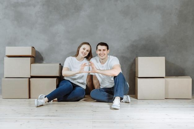 Casal feliz, homem e mulher, estão sentados no chão em um novo apartamento entre caixas de coroton e fazendo um coração com as mãos juntas.