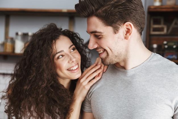 Casal feliz homem e mulher sorrindo e se abraçando na cozinha moderna de casa