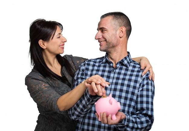 Casal feliz, inserindo uma moeda em um cofrinho
