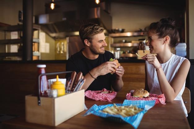 Casal feliz interagindo enquanto fast food