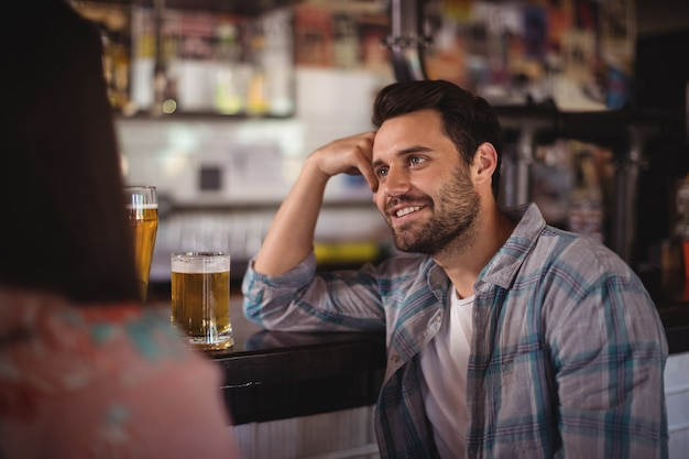 Casal feliz interagindo enquanto toma cerveja no balcão