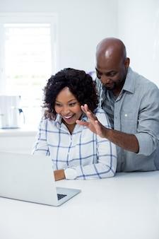 Casal feliz interagindo uns com os outros enquanto estiver usando o laptop