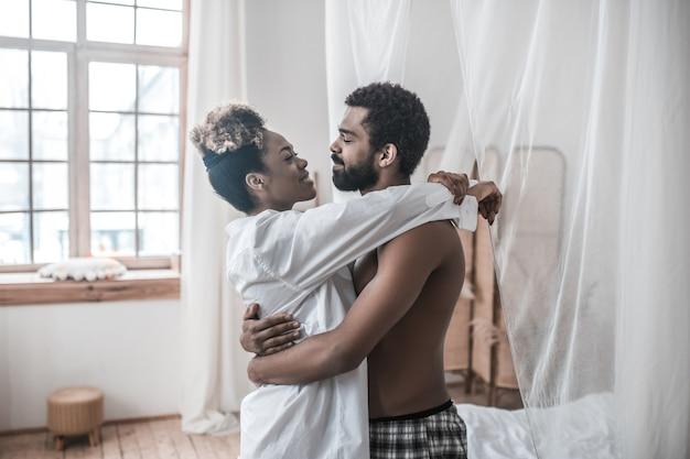 Casal feliz. jovem barbudo de pele escura e linda esposa se abraçando, olhando um para o outro em casa pela manhã