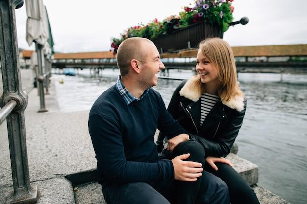 Casal feliz. jovem casal apaixonado senta-se no cais, olhando para o outro e sorrindo.