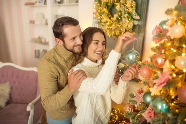 Casal feliz. jovem casal feliz em pé perto da árvore de natal e parecendo feliz