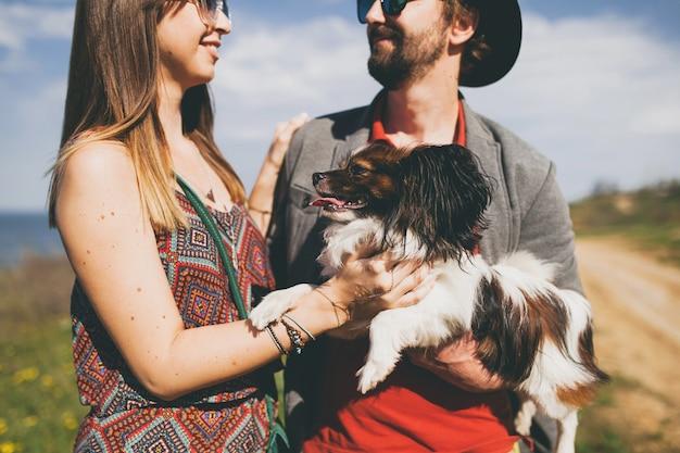 Casal feliz, jovem e elegante hippie apaixonado, caminhando com um cachorro no campo