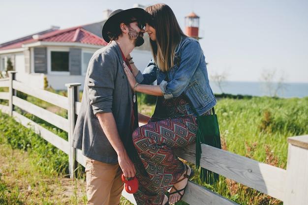 Casal feliz, jovem e elegante hippie apaixonado, caminhando pelo campo, estilo boho fashion