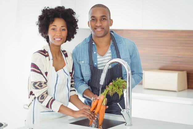 Casal feliz lavar as cenouras na cozinha