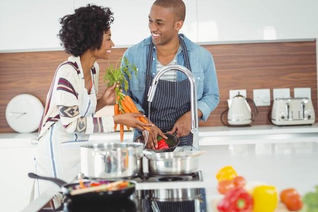 Casal feliz lavar legumes na cozinha
