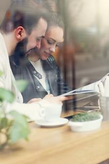 Casal feliz lendo guia em restaurante