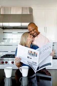Casal feliz lendo jornal juntos na cozinha