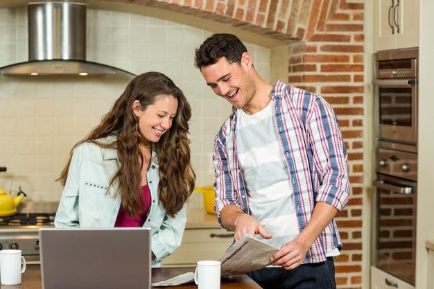 Casal feliz lendo jornal na cozinha enquanto tomando café da manhã