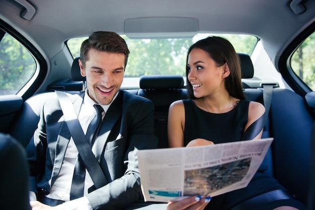 Casal feliz lendo jornal no carro