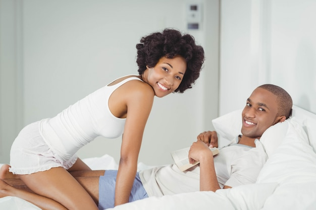 Casal feliz lendo na cama em casa