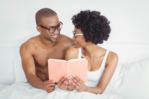 Casal feliz lendo um livro juntos