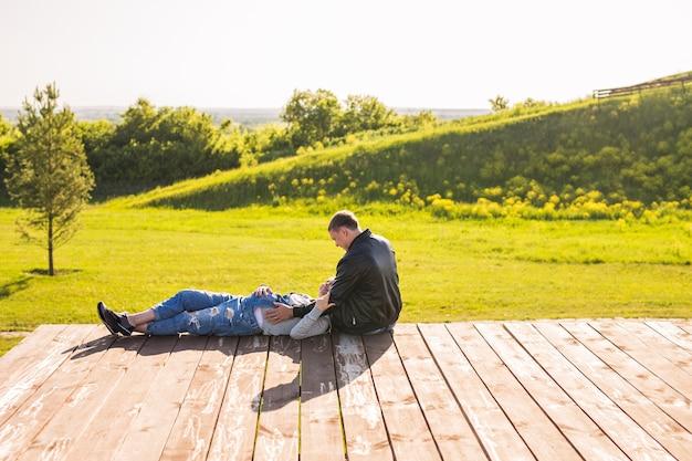 Casal feliz - marido e mulher grávida relaxando na natureza do outono.