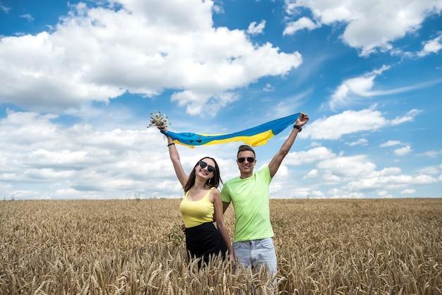 Casal feliz molda com bandeira da ucrânia no campo de trigo. estilo de vida